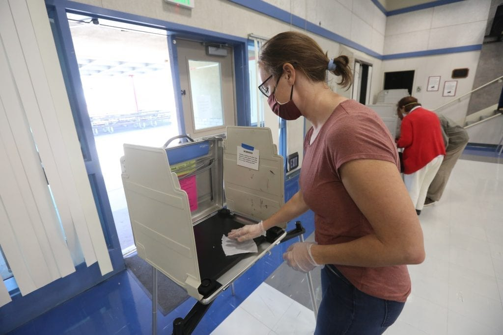 A California poll worker sanitizes a voting booth following its use at a Voter Assistance Center during the 2020 General Election.
